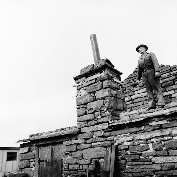 (Jimmie O'Lochend). On his roof of Lochend, fixing his chimney. North Ronaldsay.