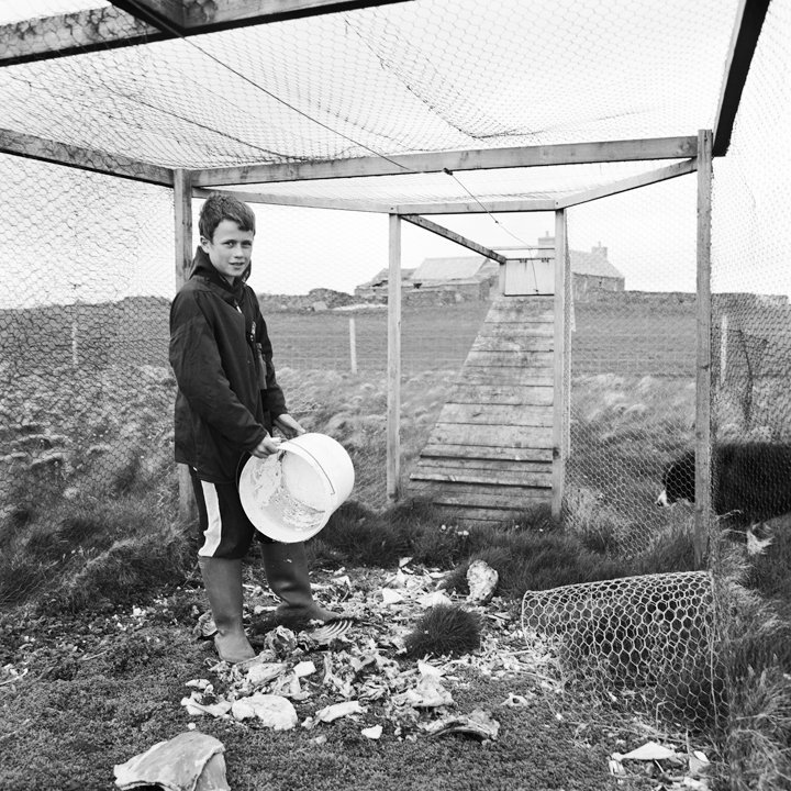 Gavin O'Twingness). The youngest islander when this was taken, pictured here in a bird catching cage in order to ring and monitor birds. He has just put out some North Ronadlsay Mutton Bones down to attract the birds. 2010.