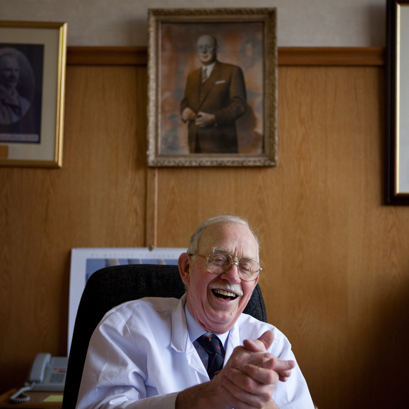 Mr Boyd Tunnock, grandson of the founder of the company. - aged 80, in his office, with an image of his father above him.