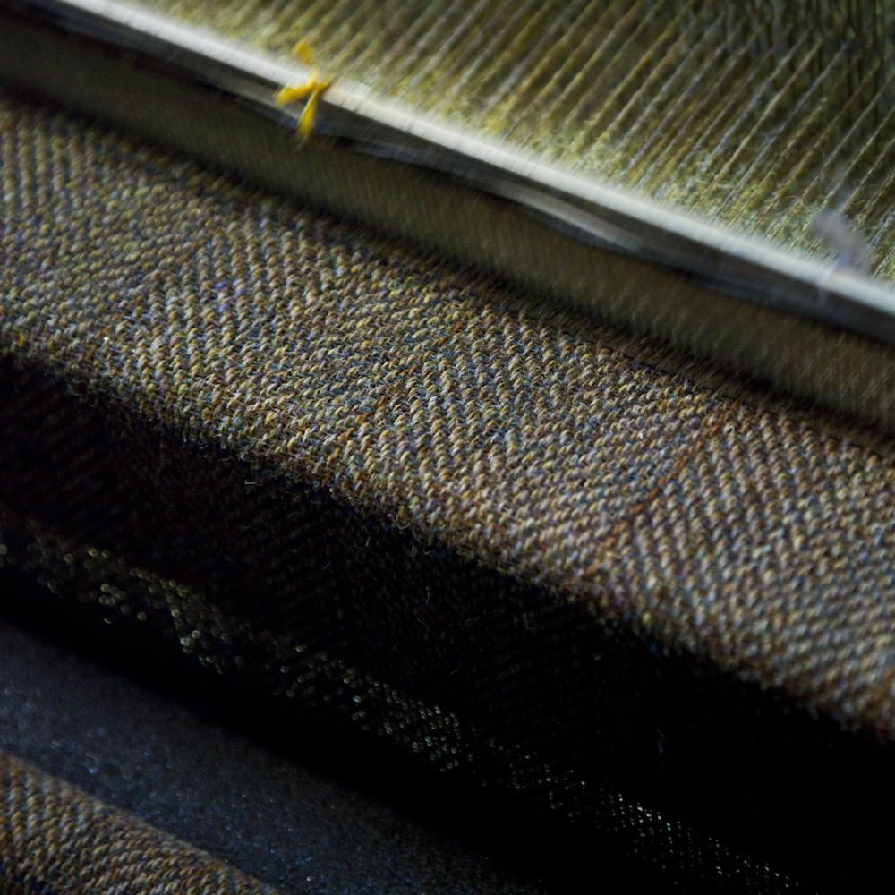 Tweed emerging from the loom. Lewis, 2009. The subtle pattern of the tweed being woven in Alexander Smith's loom shed in Carloway contains a myriad of colours. ©Robin Mitchell, all rights reserved.