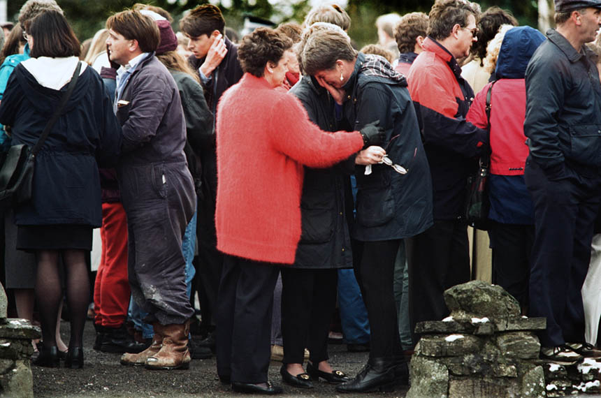 A crying woman is comforted outside Dunblane primary school. Photograph © Colin McPherson 1996, all rights reserved.