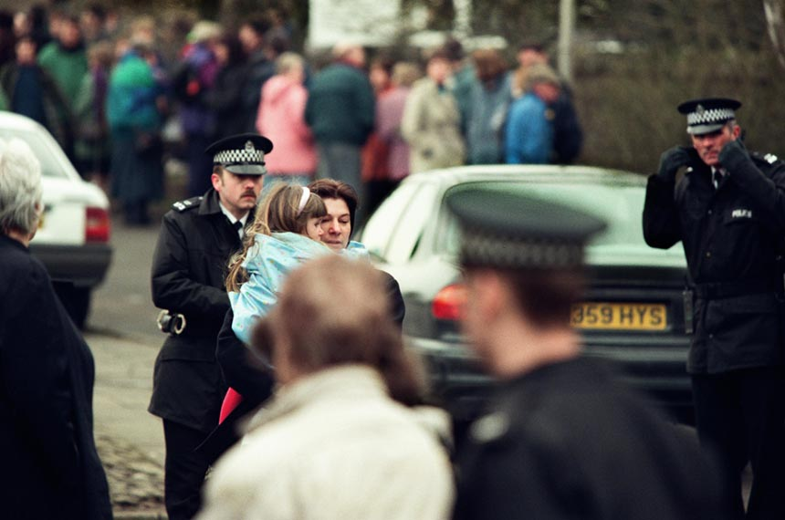 A young girl is carried away. Photograph © Colin McPherson 1996, all rights reserved.
