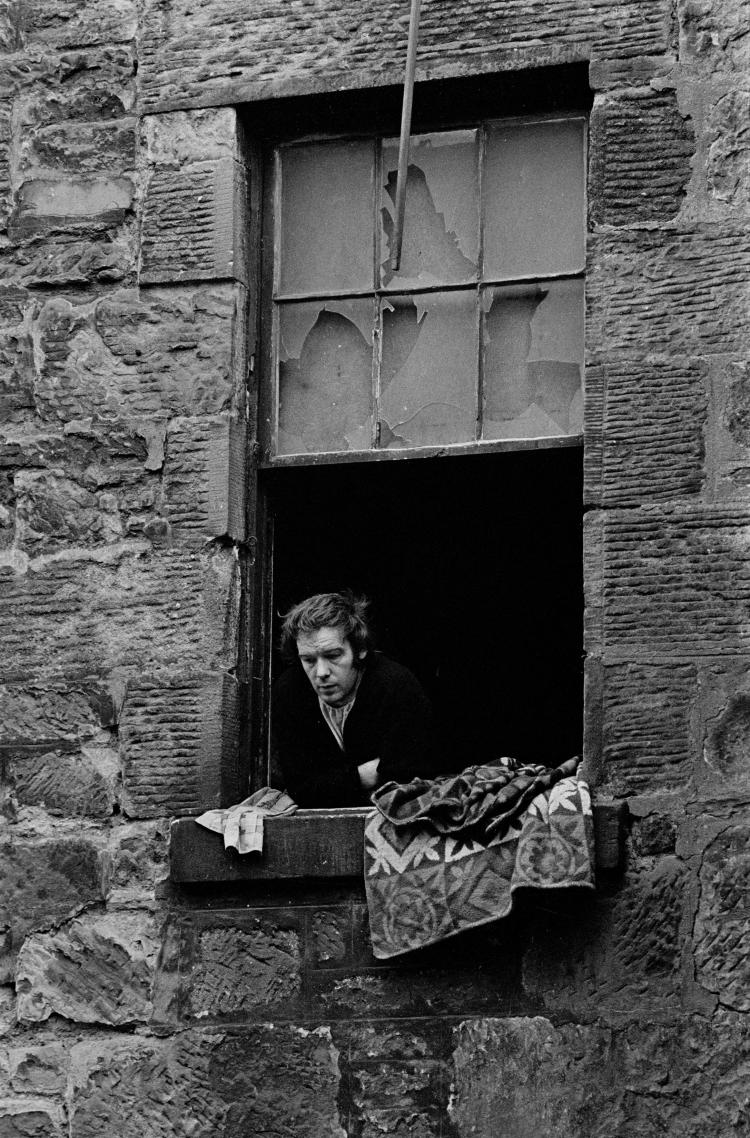 """Unemployed colliery worker Glasgow tenement © Nick Hedges/Shelter 1971 """"They are the grimmest environment that I've encountered. This has something to do with the size of the stone used in their construction, the entry to them through the cave like entrances, the deep and dark stairwells and the relentless pattern of streets. The tenements are built around a courtyard which becomes a battlefield and refuse dump."""" -  Nick Hedges"""
