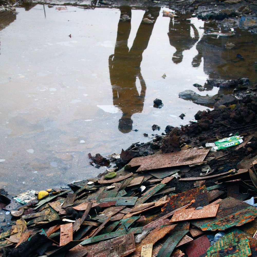 """A boy looks out over a pool of polluted water at a pile of discarded circuit boards in the slum town of Mandoli on the outskirts of Delhi. From the series """"E-wasteland"""" © Sophie Gerrard 2006, all rights reserved."""