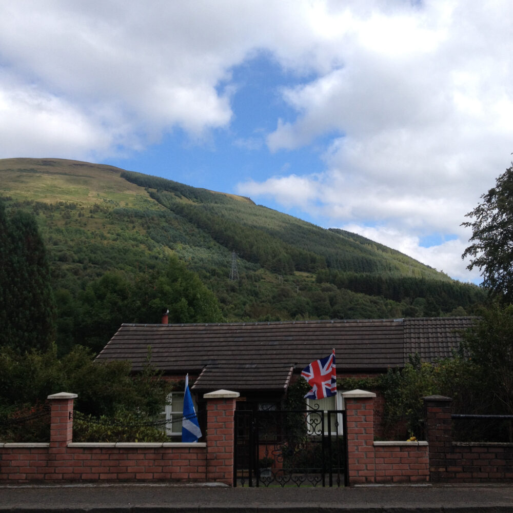 Union Flag and St Andrews Cross fly from a front garden in Argyll, Scotland. © Sophie gerrard 2014 all rights reserved.