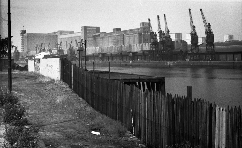 Govan, July 1977. aken from the bottom of Water Row in Govan this view shows what was the Meadowhall Granary on the north side of the Clyde. This whole vista has disappeared now, replaced by modern flats. ©Peter Degnan.
